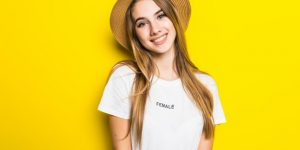 cute-smiling-model-white-t-shirt-hat-among-orange-background-with-funny-face_231208-4900