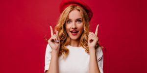 ecstatic-white-girl-beret-posing-with-amazement-elegant-caucasian-female-model-t-shirt-standing-red-wall_197531-11462
